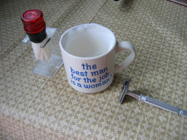 A razor, shaving brush, and mug with shaving soap in it. The mug is labeled 'The best man for the job is a woman!'