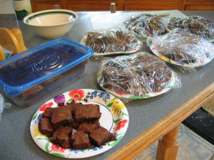 Photo of six plates and one tupperware box of brownies.